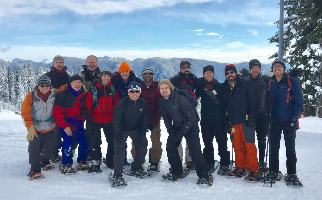 The crew posing on snow in front of blue sky