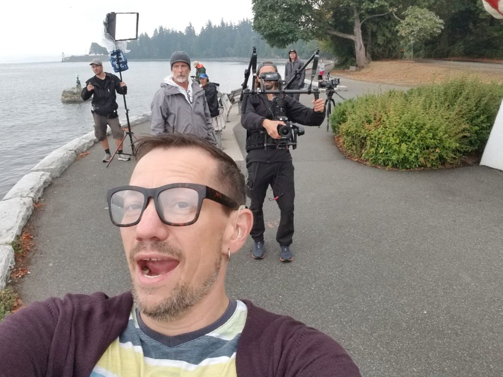 Happy guy with glasses in foreground with film crew in background, on seawall.