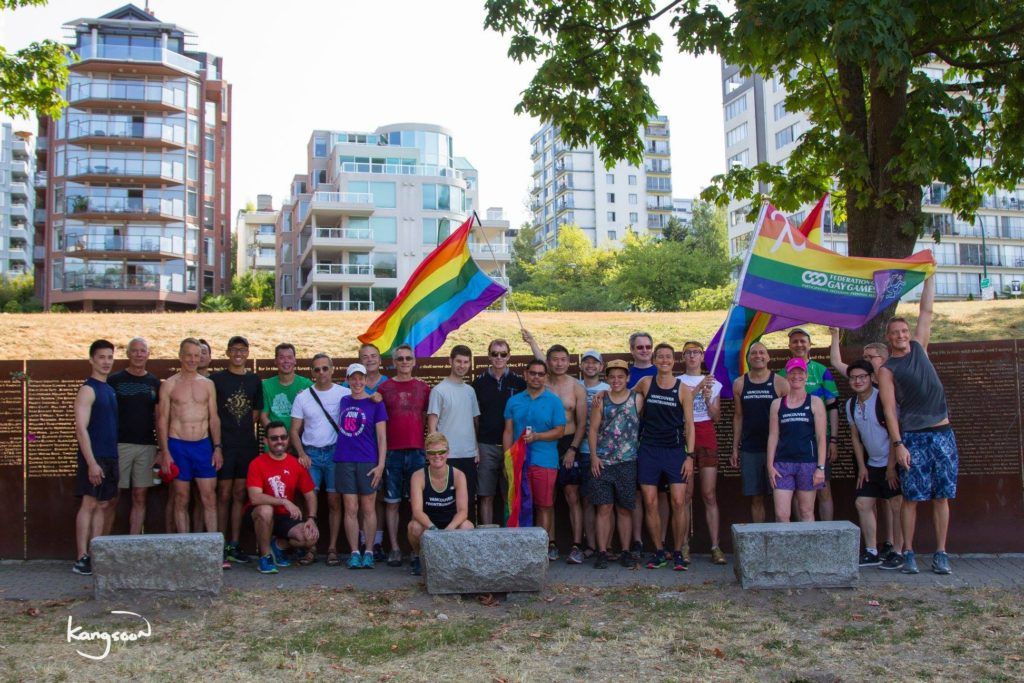 Crowd in running gear with Rainbow Flags. Standing at a lower level with city in the background